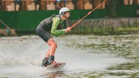 Parque extremo, Kiev, Ucrania - pueden, 07, 2017 - un salto practicado del hombre joven en Wakeboarding Foto que procesa el grano Imagenes de archivo