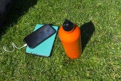 Parque herboso verde del césped con el smartphone litening al agua b de la música Foto de archivo libre de regalías
