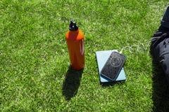 Parque herboso verde del césped con el smartphone litening al agua b de la música Fotografía de archivo libre de regalías