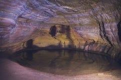 Parque nacional de Ibitipoca en la cueva del Brasil con poca iluminación y un pequeño lago foto de archivo