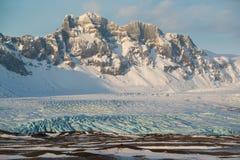 Parque nacional de Skaftafell, lengua del glaciar abajo del valle en invierno, hielo azul y montañas coronadas de nieve, Islandia Fotografía de archivo