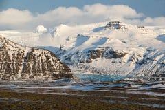 Parque nacional de Skaftafell, lengua del glaciar abajo del valle en invierno, hielo azul y montañas coronadas de nieve, Islandia Fotos de archivo