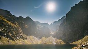 Parque nacional de Tatra, Polônia O lago Czarny Staw calm sob Rysy e as montanhas do verão ajardinam Luz do sol com raios de sol filme