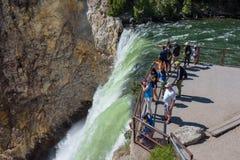 PARQUE NACIONAL DE YELLOWSTONE, WYOMING, LOS E.E.U.U. - 17 DE JULIO DE 2017: Turistas y un guía turístico que mira y que toma imá Fotos de archivo