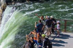 PARQUE NACIONAL DE YELLOWSTONE, WYOMING, LOS E.E.U.U. - 17 DE JULIO DE 2017: Un guía turístico señala algo de interés a su grupo  Imagen de archivo libre de regalías