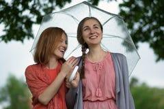 Parque que camina de dos mujeres en lluvia y charla Amistad y comunicación de la gente Fotografía de archivo