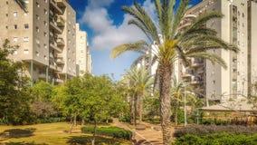 Parque verde hermoso entre condominios de varios pisos Foto de archivo