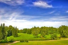 Parque verde sob o céu azul com nuvens Imagens de Stock Royalty Free