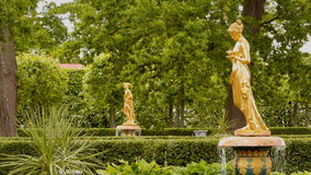 Parque y estatua en estilo antiguo - muchacha cerca del palacio de Monplaisir en Peterhof
