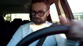 Parquean al hombre en vidrios en un coche en un estacionamiento al aire libre en la puesta del sol almacen de video