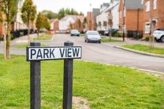 Parquee los posts de placa de calle de la visión sobre nuevo estado construido foto de archivo