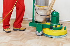 Parquet Floor maintenance by grinding machine. Carpenter doing parquet Wood Floor polishing maintenance work by grinding machine royalty free stock photos