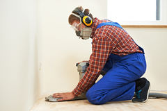 Parquet Floor maintenance by grinding machine. Carpenter doing parquet Wood Floor polishing maintenance work by grinding machine stock images