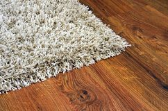Parquet floor of the wooden planks and white carpet. Parquet floor of the brown wooden planks and white shaggy carpet Royalty Free Stock Image