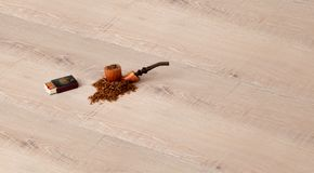 Parquet flooring with pipe, tobacco and matches. Elegance brown parquet flooring with pipe, tobacco and matches Stock Photography