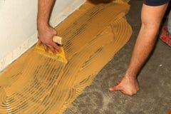 Worker laying parquet flooring. Worker installing wooden laminate flooring. Parquet flooring. Worker laying parquet flooring royalty free stock images