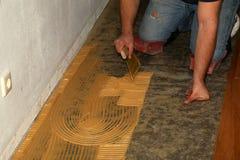 Worker laying parquet flooring. Worker installing wooden laminate flooring. Parquet flooring. Worker laying parquet flooring royalty free stock photo
