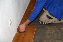 Worker laying parquet flooring. Worker installing wooden laminate flooring. Parquet flooring. Worker laying parquet flooring stock photography