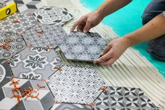 Parqueter - équipez étendre des tuiles d'hexagone sur le plancher Photographie stock libre de droits