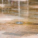 Parquetez le jour d'été chaud carrelé urbain de secteur de fontaine de jet photo libre de droits
