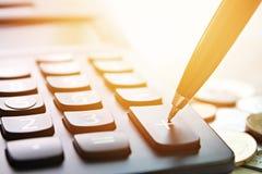 Parquez la presse sur la calculatrice plus de bouton et les pièces de monnaie sur la table de bureau photos stock