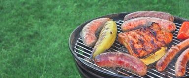 Parrilla caliente del Bbq con la carne clasificada en el césped del jardín Foto de archivo