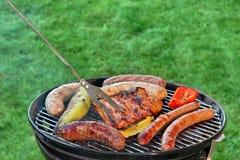 Parrilla caliente del Bbq con la carne clasificada en el césped del jardín Imagenes de archivo