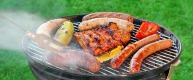 Parrilla caliente del Bbq con la carne clasificada en el césped del jardín Fotografía de archivo libre de regalías