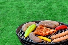Parrilla caliente del Bbq con la carne clasificada en el césped del jardín Fotos de archivo