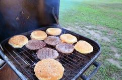 Parrilla de la barbacoa con las empanadas de la hamburguesa y los bollos de hamburguesa que cocinan en ella fotos de archivo libres de regalías