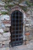 Parrilla de puerta en una pared de ladrillo vieja. Imagen de archivo libre de regalías