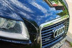 Parrilla del coche de Audi con el logotipo del cromo y la capilla delantera con gotas de la lluvia y reflexi?n del cielo y de la  fotos de archivo libres de regalías