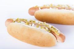 Parrilla del perrito caliente con la mostaza, la cebolla y las salmueras aisladas en blanco Imagen de archivo libre de regalías