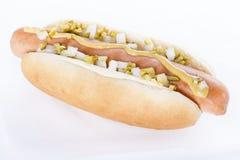 Parrilla del perrito caliente con la mostaza, la cebolla y las salmueras aisladas en blanco Foto de archivo libre de regalías