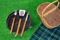 Parrilla portátil de la barbacoa en césped, las herramientas, cesta de la comida campestre y Blanke Fotos de archivo libres de regalías