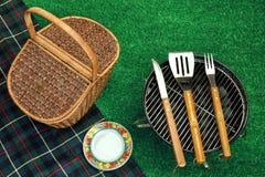 Parrilla portátil de la barbacoa en césped, las herramientas, cesta de la comida campestre y Blanke imagen de archivo