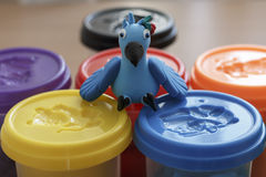 Parrot from clay on the container with clay Stock Images
