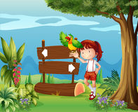 A parrot and a girl beside a signboard in the forest Royalty Free Stock Images