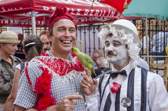 Parrot kisses man. Man dressed as clown lets his budgerigar kiss a man from the public at a public fair, Bucharest, RomanianPhoto taken on: July, 2014 Royalty Free Stock Photo
