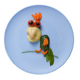 Parrot made of vegetables on blue plate Stock Image