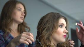 Parrucchiere che applica lacca per capelli su capelli castana nel salone di bellezza video d archivio