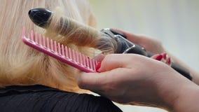 Parrucchiere che consuma le tenaglie dei capelli per i capelli biondi d'arricciatura della fine del modello di bellezza stock footage