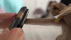 Parrucchiere che consuma le tenaglie dei capelli per la fine d'arricciatura dei capelli Elabori creare l'acconciatura e l'arricci stock footage
