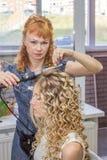 Parrucchiere che fa acconciatura alla giovane donna Fotografia Stock