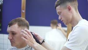 Parrucchiere che fa taglio di capelli con il rasoio elettrico Taglio di barbiere stock footage