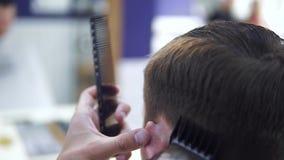 Parrucchiere che fa taglio di capelli con il rasoio elettrico Taglio di barbiere video d archivio