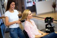 Parrucchiere che fa taglio di capelli per le donne nel salone di lavoro di parrucchiere fotografia stock libera da diritti