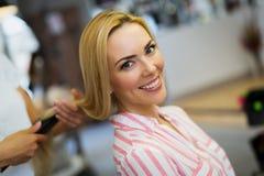 Parrucchiere che fa taglio di capelli per le donne nel salone di lavoro di parrucchiere immagine stock libera da diritti