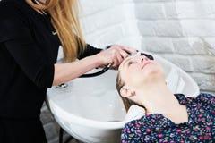 Parrucchiere che lava capelli biondi femminili Movimento lento fotografia stock