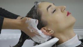 Parrucchiere che lava i capelli dei clienti in un bacino moderno nel suo salone di lavoro di parrucchiere come prepara disegnare  archivi video